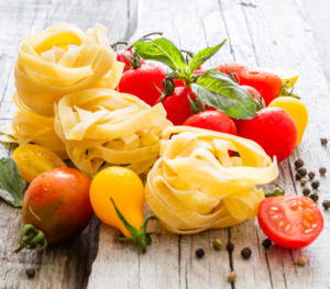 Raw pasta tomato basil rustic wood background
